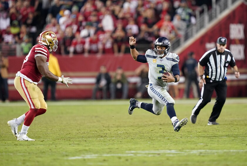 Seahawks quarterback Russell Wilson runs with the ball during a game against the 49ers on Nov. 11 at Levi's Stadium.