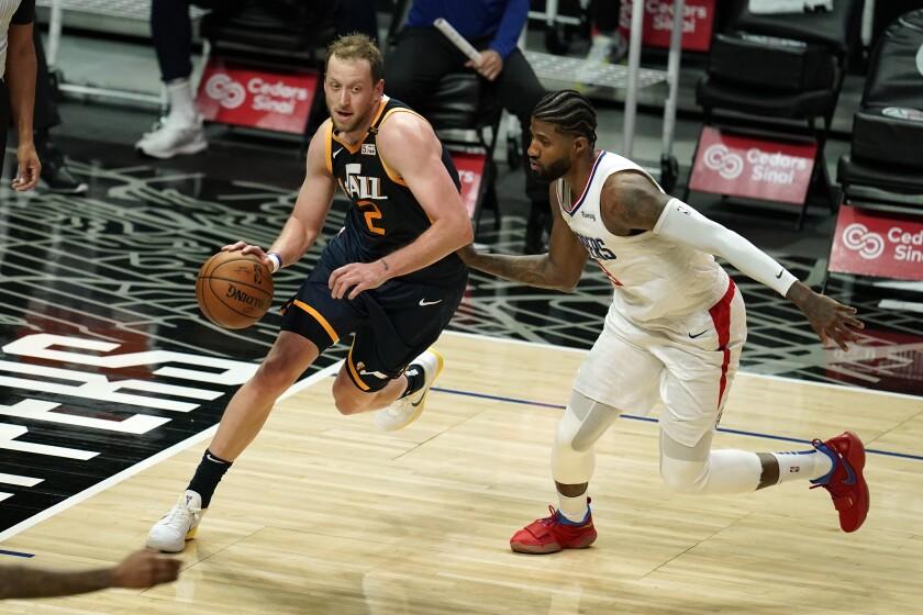 Utah Jazz forward Joe Ingles dribbles past Clippers guard Paul George.