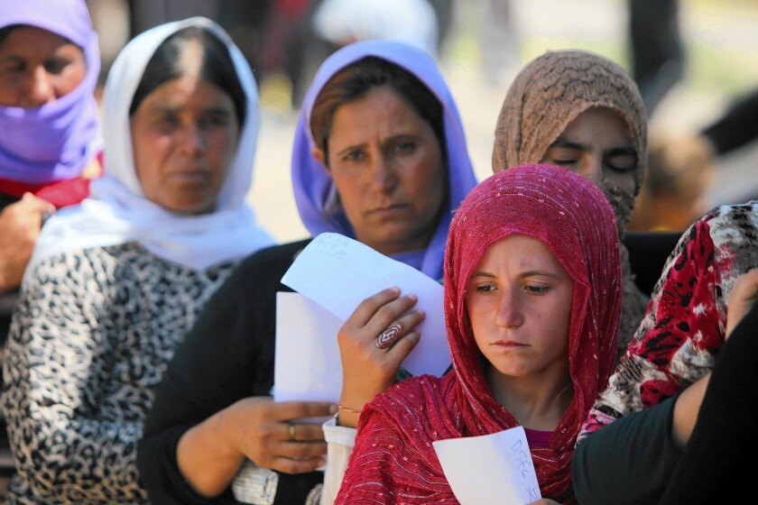 Yazidi women wait in line for food at a camp for the displaced in Iraqi Kurdistan's Dahuk province.