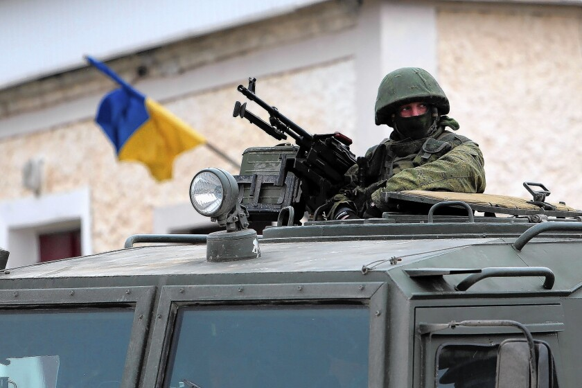 Pro-Russia forces are deployed outside a Ukrainian military base near Simferopol, the capital of Crimea. Russia has reportedly beefed up its military presence in the Ukrainian peninsula.