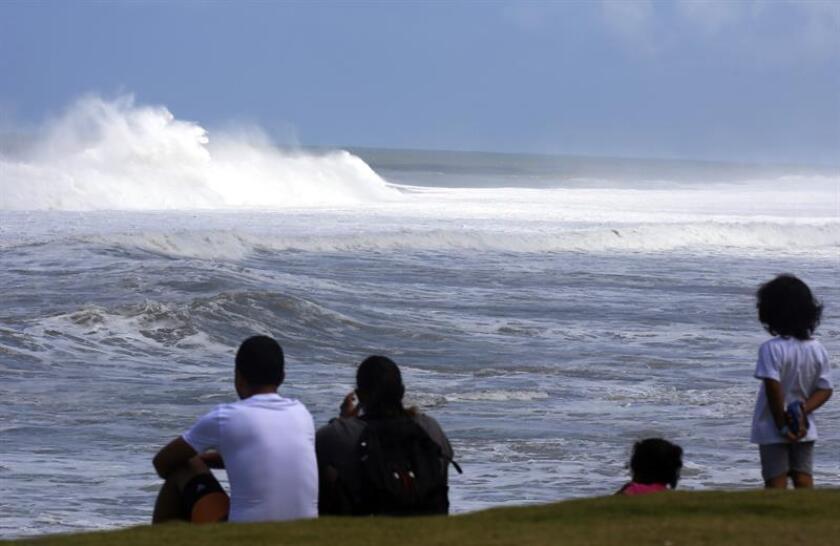 Unas personas observan las fuertes olas en el histórico asentamiento La Perla en el Viejo San Juan, Puerto Rico. EFE/Archivo