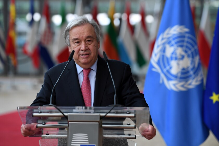 António Guterres stands at a lectern with a blue and white flag next to him