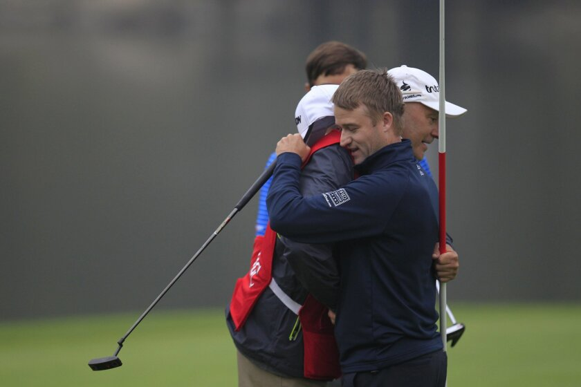 Russell Knox, right, of Scotland embraces his caddy on the 18th hole after the final round of the HSBC Champions golf tournament at the Sheshan International Golf Club in Shanghai, China Sunday, Nov. 8, 2015. (AP Photo)