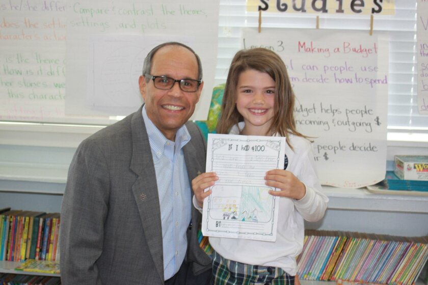 President/CEO of Father Joe's Villages and Stella Maris Deacon Jim Vargas with first-grader Mariella Smith and her letter about wanting to help homeless people.