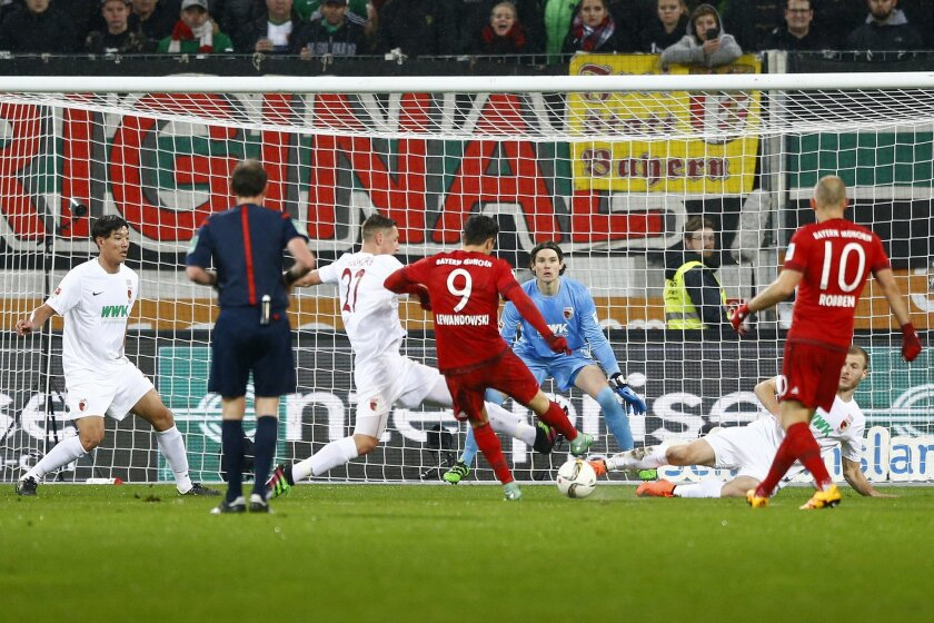 Bayern's Robert Lewandowski (9) scores his side's opening goal during the German first division Bundesliga soccer match between FC Augsburg and FC Bayern Munich at the WWK Arena in Augsburg, Germany, Sunday, Feb. 14, 2016. (AP Photo/Matthias Schrader)