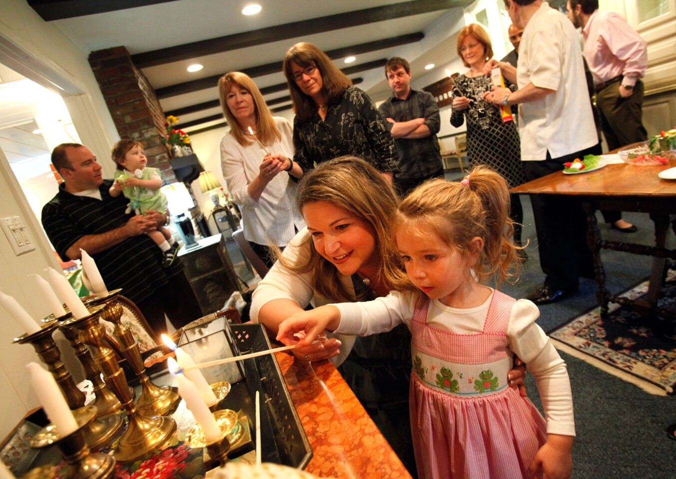 Havi Wolfson-Hall lights candles with her daughter Ellie before the Passover Seder at Ron and Susie Wolfson's home in Encino.