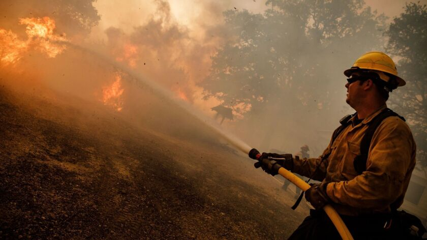 Verizon slowed critical internet service during a recent wildfire battle, according to the Santa Clara County Fire Department. Here, a firefighter battles the Mendocino Complex fire in July.