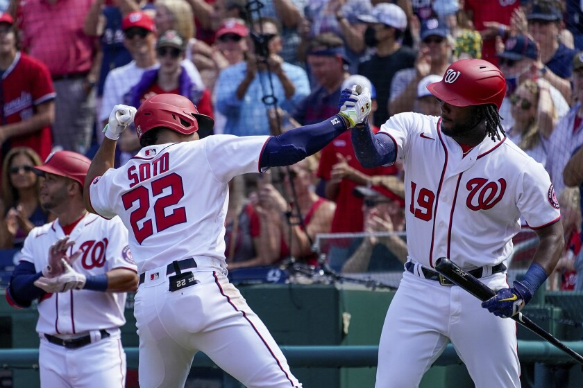 Washington Nationals' Juan Soto celebrates with teammate Josh Bell (19) after hitting a solo home run during the third inning of a baseball game against the Colorado Rockies at Nationals Park, Sunday, Sept. 19, 2021, in Washington. (AP Photo/Andrew Harnik)