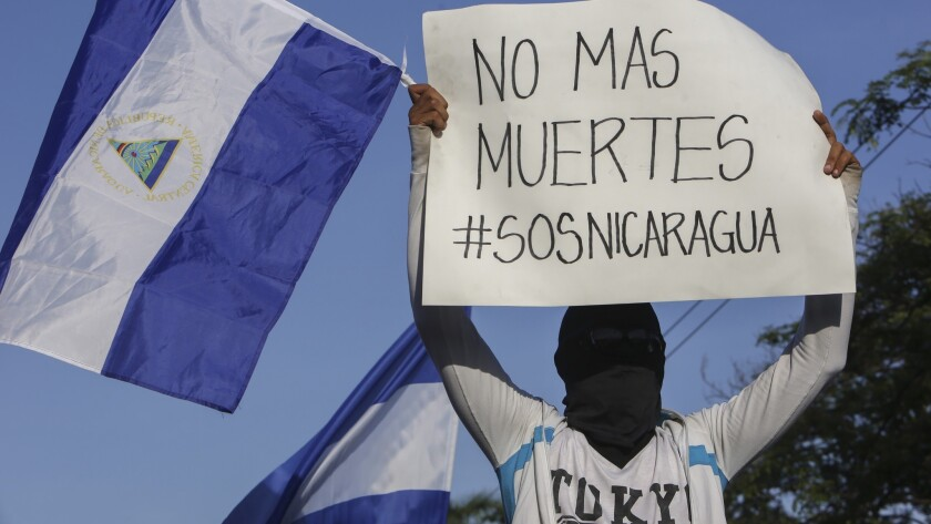 A masked demonstrator holding a Nicaraguan national flag and a sign with a message that reads in Spa