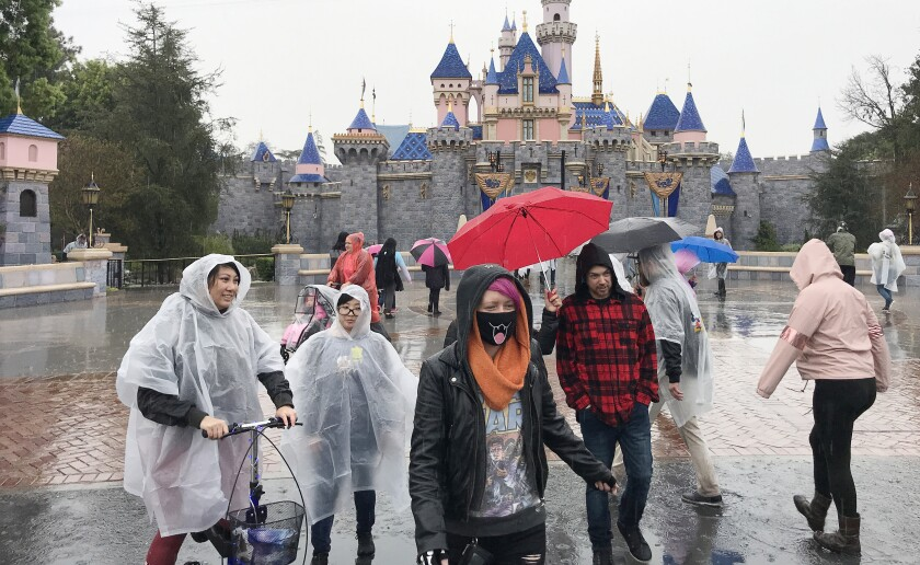 Inclement weather and coronavirus kept crowds sparse at Disneyland in Anaheim on Thursday. The park will close Saturday through the end of the month.
