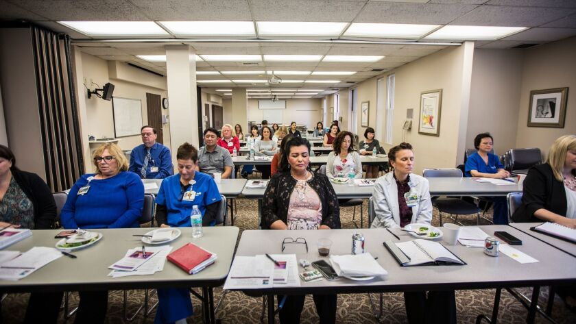 Nurses at St. Joseph Hospital in Orange participate in a breathing exercise. With recent shootings, fires and other disasters, nurses have started taking extra time to talk about their own mental health and that of other medical providers.
