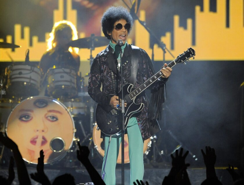FILE - In this May 19, 2013 file photo, Prince performs at the Billboard Music Awards at the MGM Grand Garden Arena in Las Vegas. A law-enforcement official says that tests show the music superstar died of an opioid overdose. Prince was found dead at his home on April 21, 2016, in suburban Minneapo