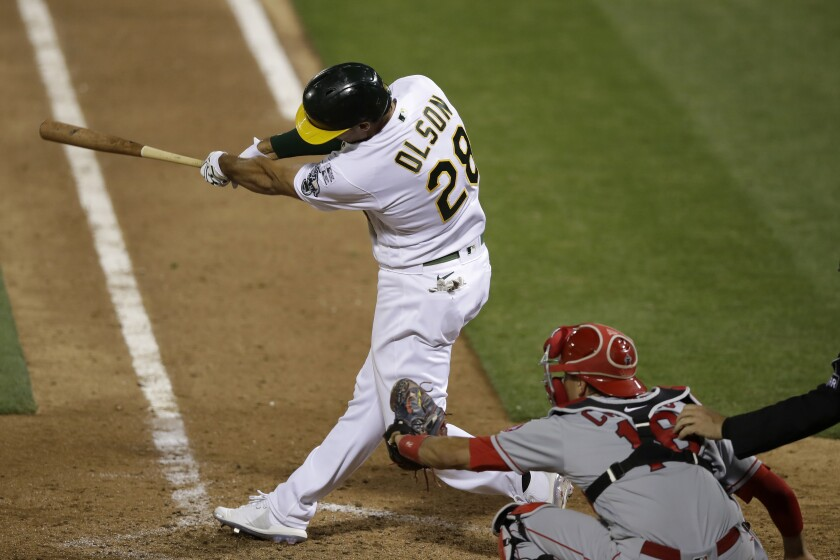 The Athletics' Matt Olson hits a walk-off grand slam in the 10th inning as Angels catcher Jason Castro, right, looks on.