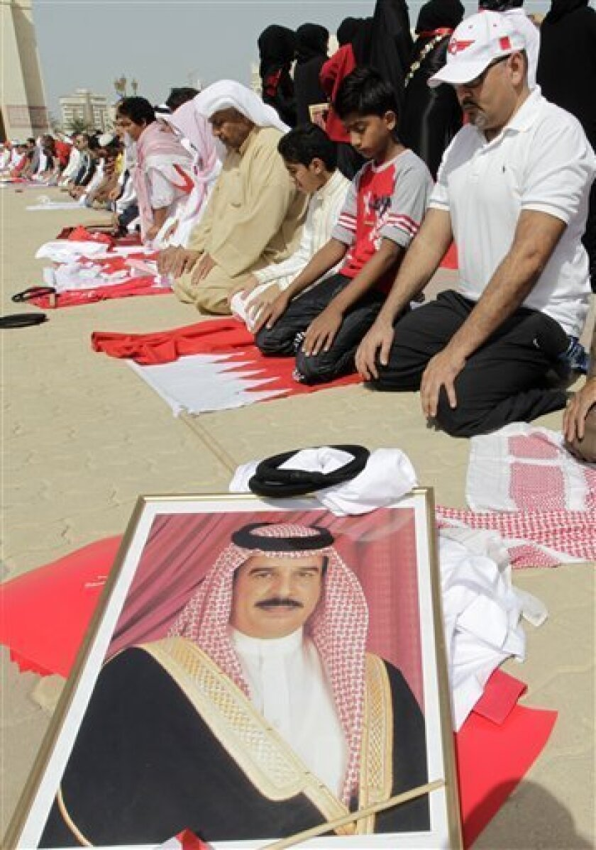 Bahraini pro government protesters pray behind a picture of the Bahraini king Hamad bin Issa Al Khalifa during Friday praying before a march supporting the Bahraini leadership in Manama, Bahrain, Friday, Feb. 18, 2011. (AP Photo/Hassan Ammar)