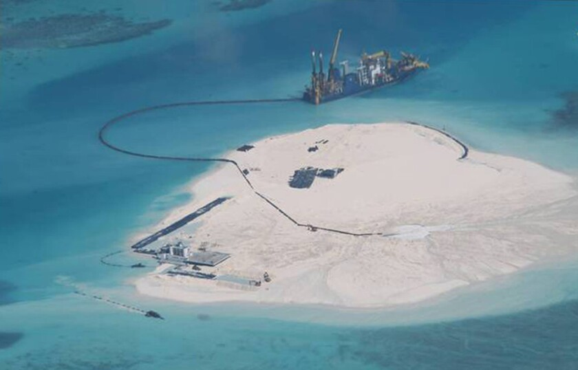 A Chinese vessel works on a building project in the Spratly Islands in 2014. New satellite images show that China has rapidly expanded its artificial islands in the South China Sea.