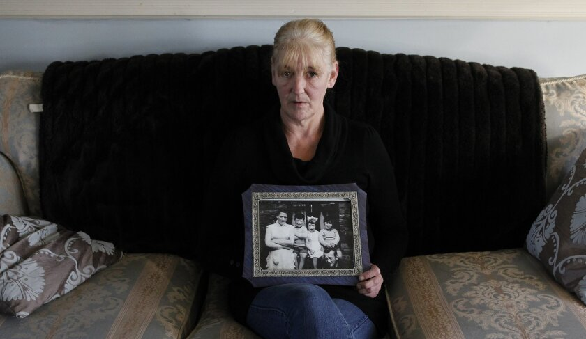 FILE - In this Thursday Jan. 12, 2012 file photo, Helen McKendry holds a family photograph showing her mother Jean McConcille, at home in Killyleagh, Northern Ireland. Police in Northern Ireland arrested Sinn Fein party leader Gerry Adams on Wednesday over his alleged involvement in the Irish Repub