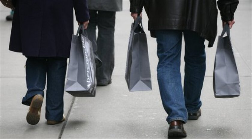 In this Nov. 26, 2008 file photo, shoppers walk along Fifth Ave. in New York. (AP Photo/Mark Lennihan, file)