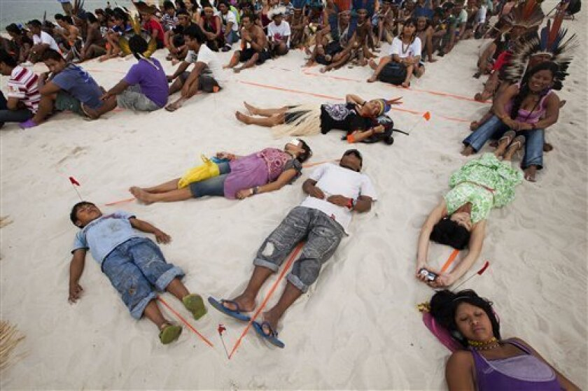 People participate in a human banner on Flamengo beach, organized by Amazon Watch, on the sidelines of the Rio+20, or UN Conference on Sustainable Development in Rio de Janeiro, Brazil, Tuesday, June 19, 2012. The activists are calling attention to threats posed to rivers, forests and livelihoods b