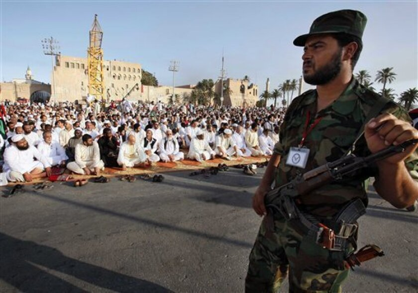 A Libyan rebel stands guard as worshippers gather in the former Green Square, renamed Martyr's Square, for the morning Eid prayer marking the end of Ramadan and to celebrate their victory over Moammar Gadhafi in Tripoli, Libya, Wednesday, Aug. 31, 2011. Libyans on Wednesday wept over the graves of those killed in their six-month war against Moammar Gadhafi, then celebrated their newfound freedom with morning prayers and joyous chants in the capital's main square _ bittersweet rituals marking the start of a major Muslim holiday. (AP Photo/Abdel Magid Al Fergany)