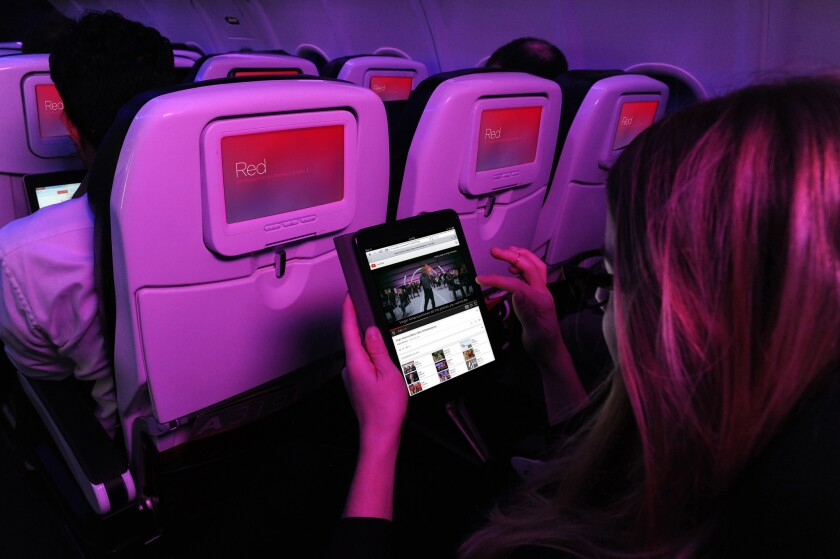 A passenger on Virgin America uses the onboard Wi-Fi. Connectivity companies may be able to speed up onboard Wi-Fi in the near future if airlines are ready to invest in new equipment.