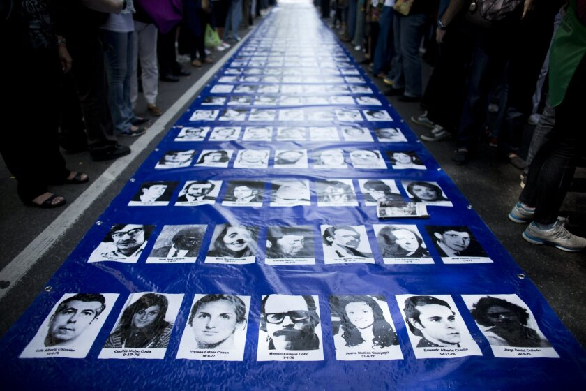 FILE - In this March 24, 2014 file photo, a banner filled with photos of people who went missing during the 1976-83 dictatorship lays on the ground before the start of a march marking the 38th anniversary of the 1976 military coup in Buenos Aires, Argentina. Four men accused of crimes against humanity during Argentina's dictatorship have decided to break a pact of silence among ex-members of the military who are on trial and collaborate with authorities in identifying victims and burial sites, a judge said Wednesday, Dec. 10, 2014. Human rights groups say about 30,000 people died or disappeared in Argentina's brutal dictatorship. (AP Photo/Victor R. Caivano, File)