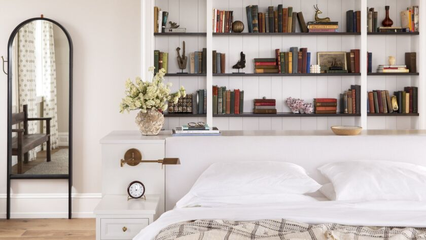In a neutral bedroom in Nantucket designed by Katie Martinez, a built-in bookcase that looks like a