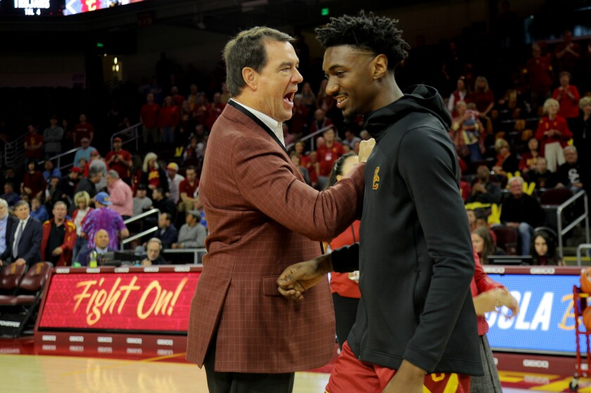 USC athletic director Mike Bohn congratulates guard Jonah Mathews during a Senior Day ceremony before the game against UCLA on March 7, 2020.
