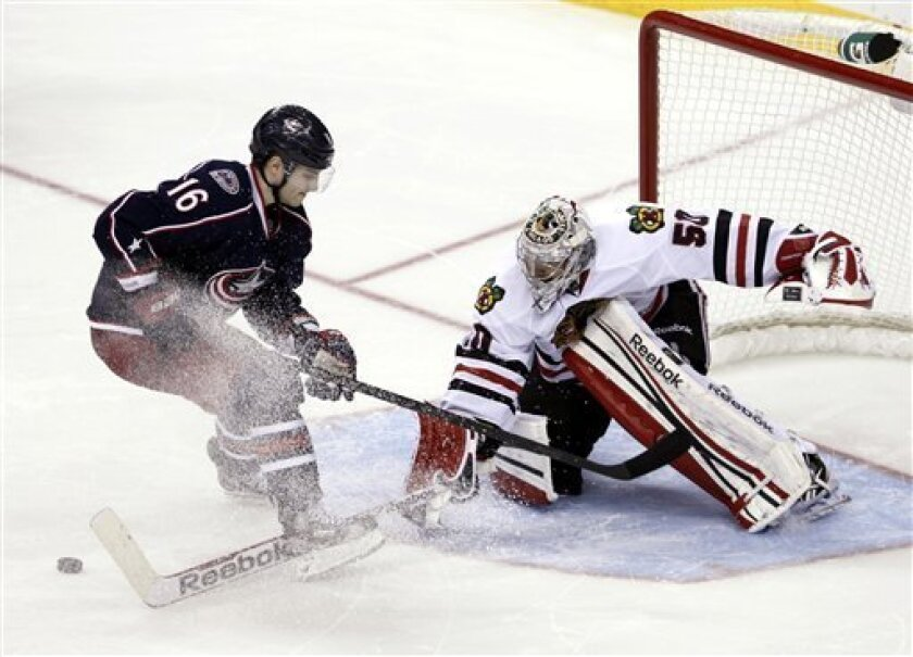 Chicago Blackhawks goalie Corey Crawford, right, stops a shot by Columbus Blue Jackets' Derick Brassard in the shootout of an NHL hockey game in Columbus, Ohio, Thursday, March 14, 2013. The Blackhawks won 2-1. (AP Photo/Paul Vernon)