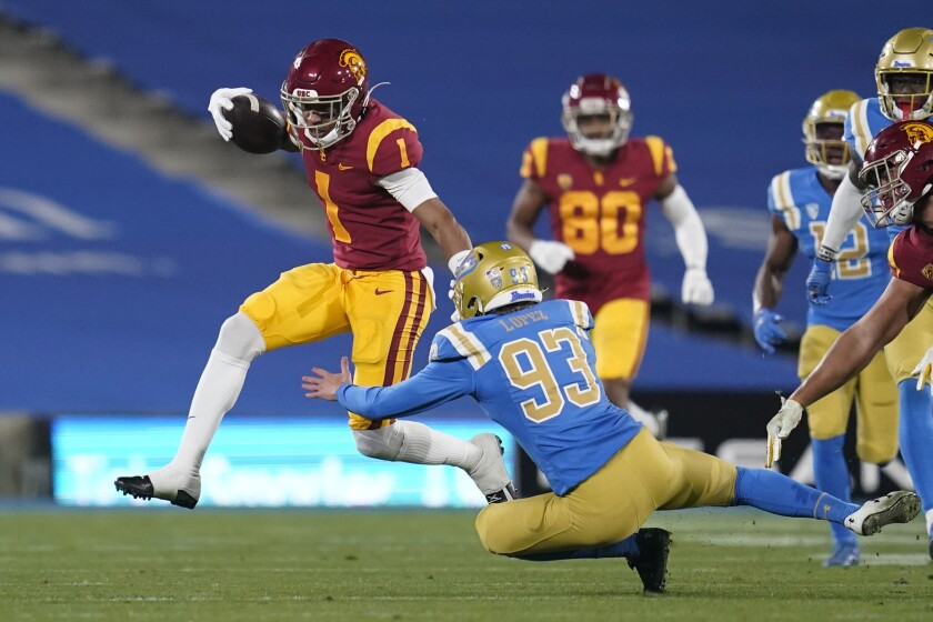 USC receiver Gary Bryant Jr. avoids a tackle by UCLA's RJ Lopez during a 2020 game.