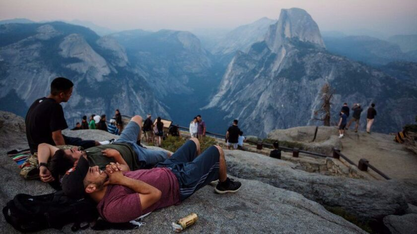 Yosemite National Park visitors gather at a viewing spot for Half Dome, shrouded by smoke from nearby fires, in July. The National Park Service is considering raising fees during peak months for the most popular parks, including Yosemite.