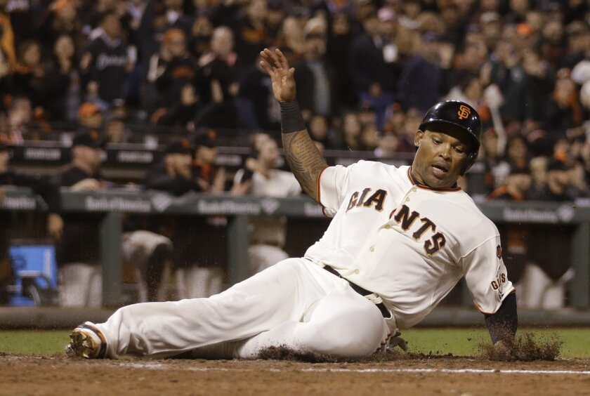 FILE - In this Tuesday, Sept. 15, 2015 file photo, San Francisco Giants' Marlon Byrd slides to score against the Cincinnati Reds in the sixth inning of a baseball game in San Francisco. The Giants declined their 2016 contract options on outfielders Byrd and Nori Aoki. Both players became free agent