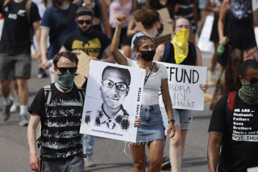 Fotografía de archivo del 27 de junio de 2020, de manifestantes con pancartas mientras marchan por Sable Boulevard durante una manifestación por la muerte de Elijah McClain en Aurora, Colorado. (AP Foto/David Zalubowski, Archivo)