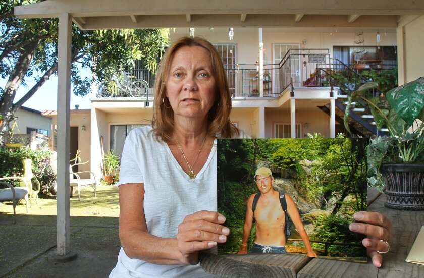 Mary Lappies, 59, at her Oceanside apartment complex with a photo of her son Jason, 31, who died unexpectedly last June. Mary has agreed to donate samples of Jason's body for a molecular autopsy program.