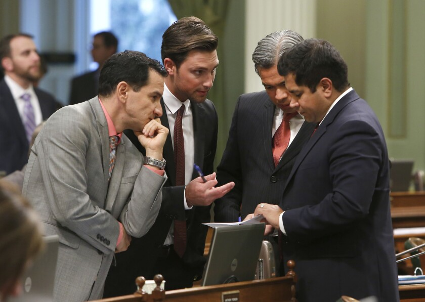 Democratic Assembly members, from left, Anthony Rendon of Lakewood, Ian Calderon, of Whittier, Rob Bonta of Alameda and Jimmy Gomez of Los Angeles, huddle during an Assembly session last year. Ian Calderon has agreed to pay fines for not disclosing income.