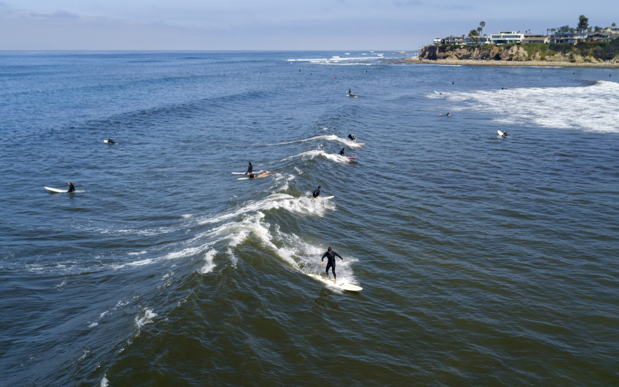A surfer rides a wave in Tourmaline Surf Park in Pacific Beach after local beaches reopened to activities such as walking, running, and surfing on April 27, 2020. Beaches have been closed for several weeks due to the coronavirus. The boardwalks are still off limits and gathering on the sand is not allowed.