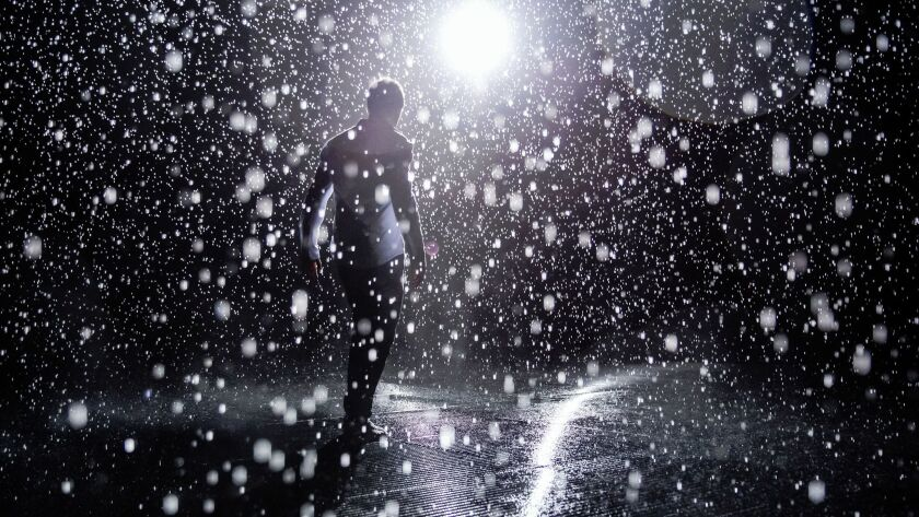 Random International's Hannes Koch test out the sensitivity of the sensors inside the Rain Room, on exhibit at LACMA in Los Angeles, Calif., on Oct. 26, 2015.