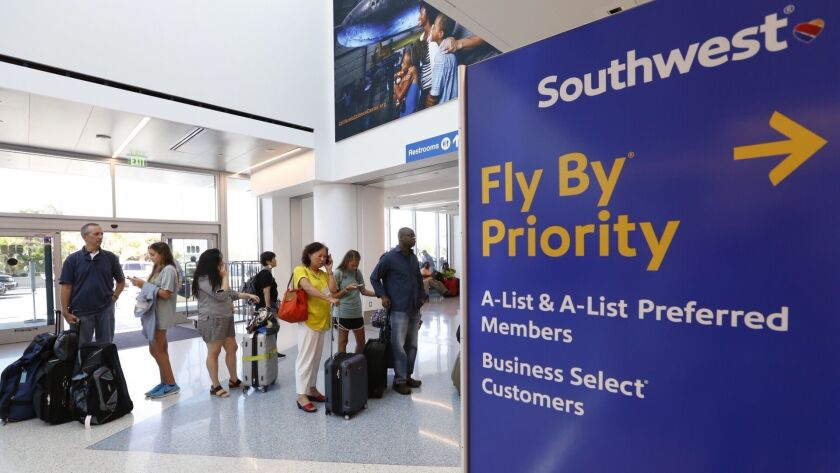 Passengers line up at the Southwest Airlines ticket counter at Los Angeles International Airport. The airline is raising its early boarding fee from $15 to as much as $25, depending on the popularity and length of the flight.