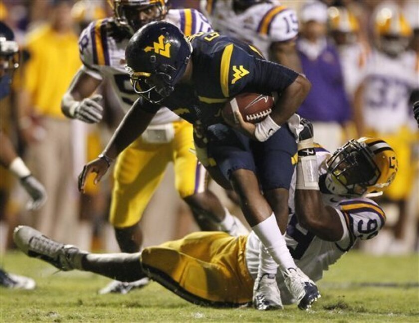 West Virginia quarterback Geno Smith is dragged to the ground by LSU defensive end Sam Montgomery during the second half of an NCAA college football game in Baton Rouge, La., Saturday, Sept. 25, 2010. LSU defeated West Virginia 20-14. (AP Photo/Patrick Semansky)