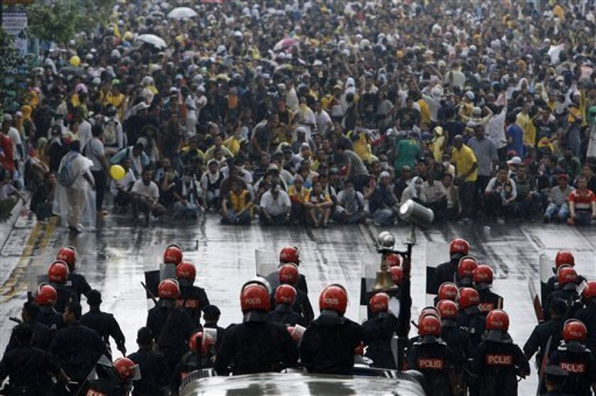 """Malaysian activists from Coalition for Clean and Fair Elections (Bersih), background, sit on a street as they face riot police during a rally in Kuala Lumpur, Malaysia, Saturday, July 9, 2011. Police fired tear gas and detained hundreds of activists as those demonstrators massed Saturday across Malaysia's main city demanding electoral reforms in the country's biggest political rally in years. The """"Bersih"""" means """"clean"""" in Malay. (AP Photo/Vincent Thian)"""