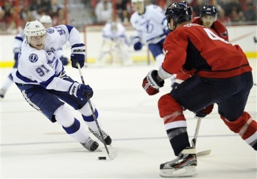 Tampa Bay Lightning center Steven Stamkos (91) skates with the puck against Washington Capitals defenseman John Erskine (4) during the second period of an NHL hockey game, Sunday, April 7, 2013, in Washington. (AP Photo/Nick Wass)