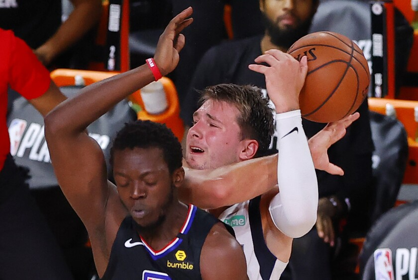 Dallas Mavericks' Luka Doncic, right, draws a foul from Los Angeles Clippers' Reggie Jackson, left, during the third quarter of Game 1 of an NBA basketball first-round playoff series, Monday, Aug. 17, 2020, in Lake Buena Vista, Fla. (Kevin C. Cox/Pool Photo via AP)