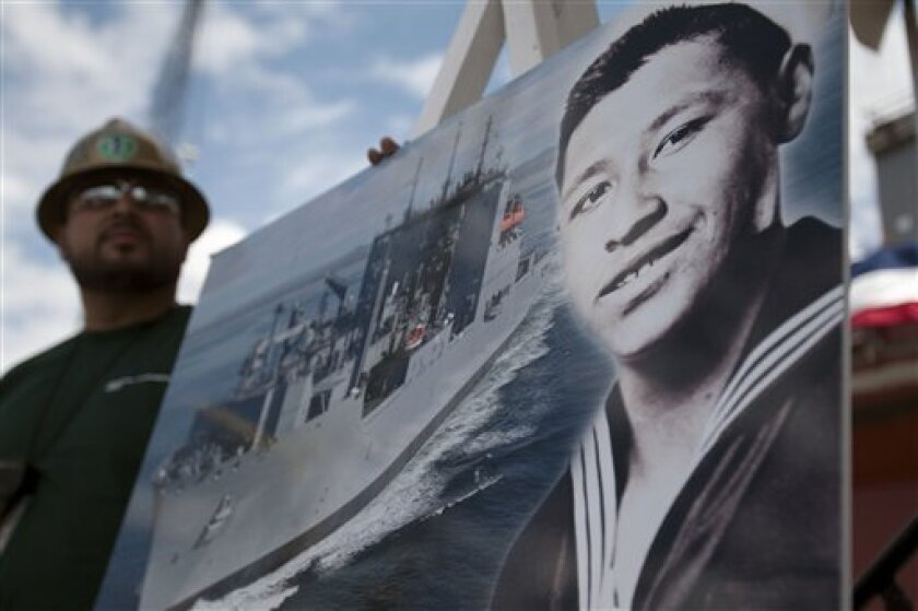Shipyard worker Julian Cruz, left, holds a picture showing the late farm labor leader Cesar Chavez during his stint in the Navy, alongside an image of a T-AKE class dry cargo and ammunition ship during a naming ceremony Wednesday, May 18, 2011, in San Diego. Navy Secretary Ray Mabus made the formal announcement Wednesday that the Navy has named the last of 14 new cargo ships after Chavez. (AP Photo/Gregory Bull)