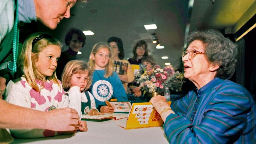 The author signs a book as children and adults wait