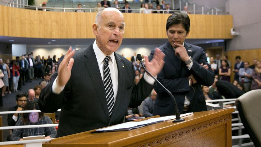 Gov. Jerry Brown, flanked by Senate President Pro Tem Kevin de León, urges members of the Environmental Quality Committee to approve a pair of bills to extend cap and trade.