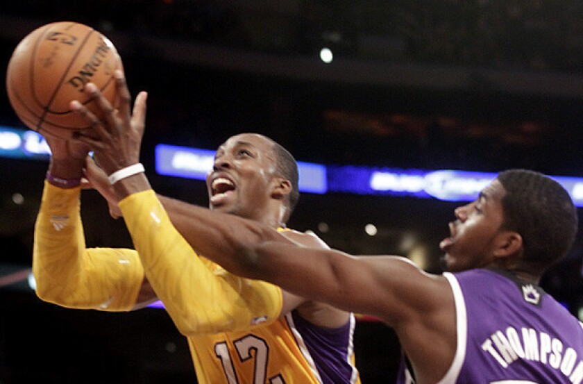 Lakers center Dwight Howard is fouled by Kings power forward Jason Thompson.