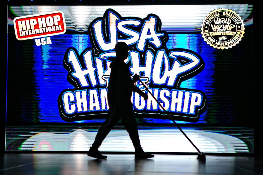 A staff member silhouetted against the logo of the 2021 USA Hip Hop Dance Championship