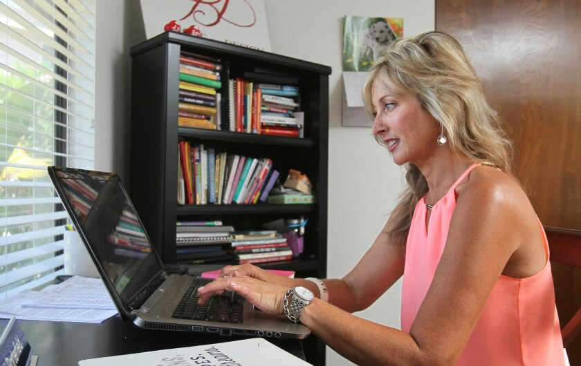 Traci Porterfield in her home office at her La Costa area home. She's the CEO and founder of Love by Design matchmaking service.