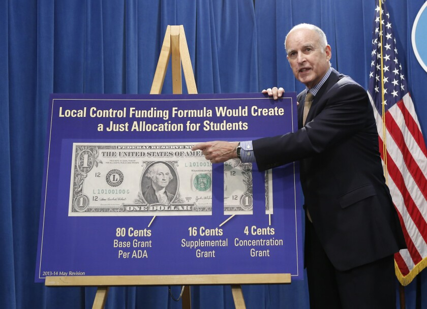 California failed to win a Race to the Top grant, but nonetheless committed itself to a new set of curriculum standards that will cost the state well over $1 billion to implement. Above: Gov. Jerry Brown gestures to a chart showing his plan to give more local control over education funding as he discussed his state budget plan at the Capitol in Sacramento.