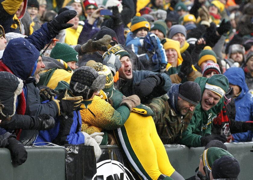 Green Bay Packers' Eddie Lacy celebrates with fans after hit touchdown run during the first half of an NFL football game against the Atlanta Falcons Sunday, Dec. 8, 2013, in Green Bay, Wis. (AP Photo/Mike Roemer)