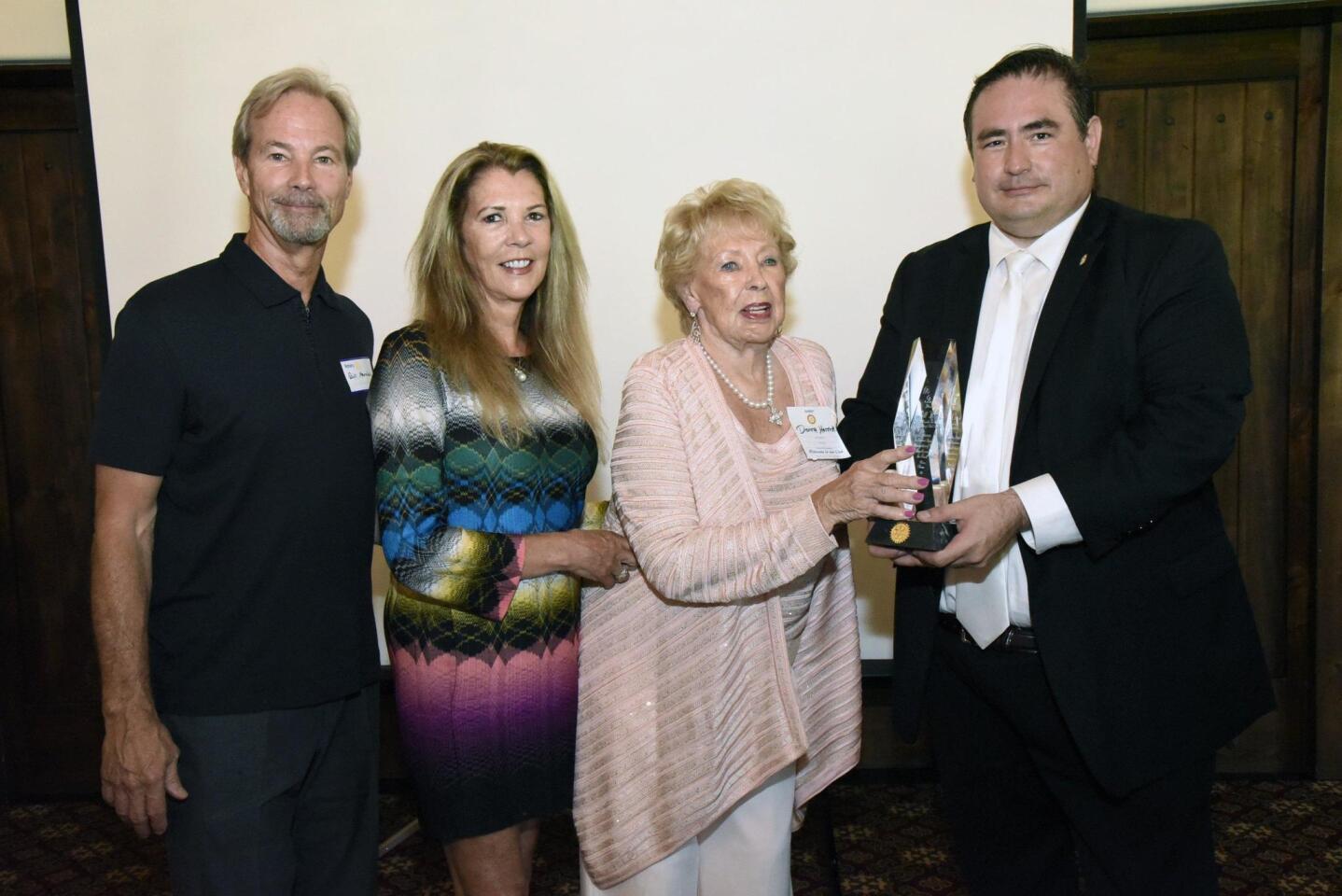 Son Bill Herrick, daughter Leann Herrick-VanLangan, and Donna Herrick are presented a posthumous award by President Luis Carranza, honoring the generosity and work of the late Bill Herrick